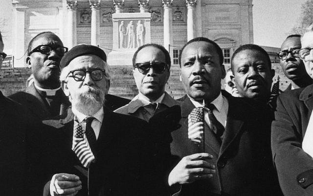 "UNSPECIFIED - MARCH 13:  ""Leaders of the protest, holding flags, from left Bishop James Shannon, Rabbi Abraham Heschel, Dr. Martin Luther King and Rabbi Maurice Eisendrath."" Tomb of the Unknown Soldier, Arlington Cemetery, February 6, 1968. Published February 7, 1968.  (Photo by Charles Del Vecchio/Washington Post/Getty Images)"