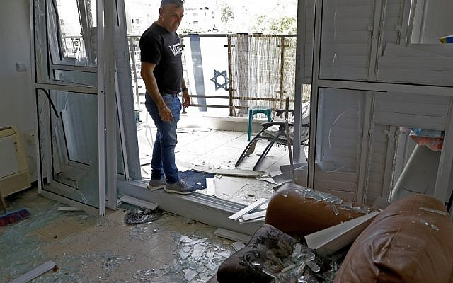 A man examines the damage inside a building on May 6, 2019, that was hit during a rocket attack from the Gaza Strip on the southern Israeli city of Ashdod (JACK GUEZ / AFP)