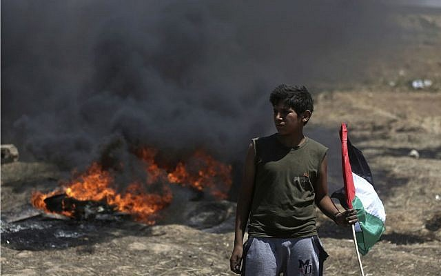 A boy holds a Palestinian flag in front of burning tires during a protest at the Gaza Strip's border with Israel, Monday, May 14, 2018.  (AP Photo/Khalil Hamra via Jewish News)