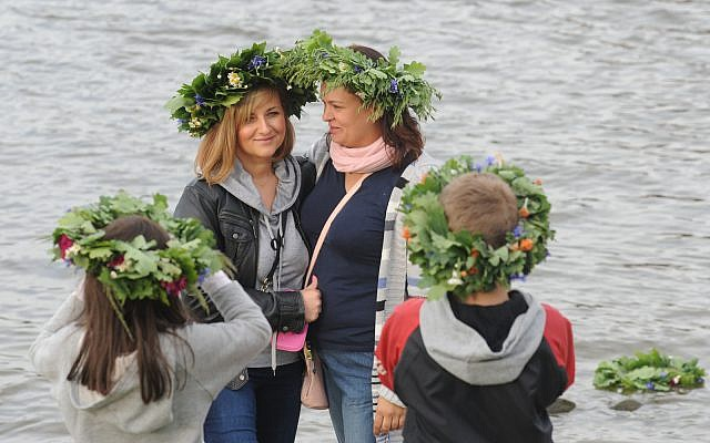 Women with traditional wreaths on their heads take photos during midsummer celebrations on the banks of the Vistula river in Warsaw, Poland, Saturday, June 21, 2014. (AP Photo/Alik Keplicz)