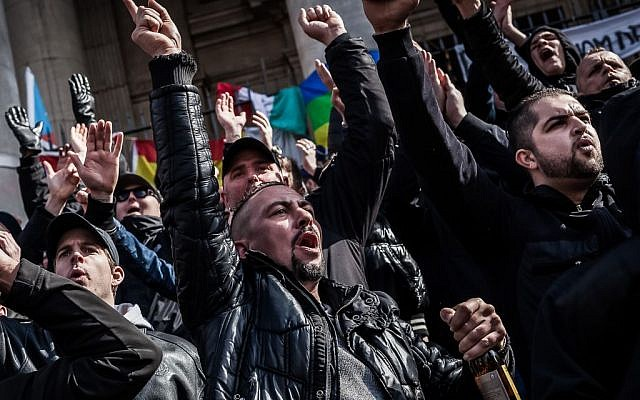 Far-right demonstrators protest at a memorial site at the Place de la Bourse in Brussels, Sunday, March 27, 2016. (AP Photo/Valentin Bianchi)