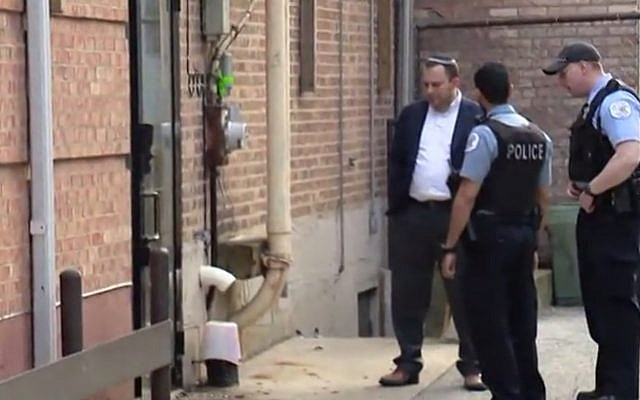 Police and Rabbi David Wolkenfeld investigating suspected arson outside Anshei Sholom B'nei Israel synagogue in Chicago on May 19, 2019. (screen capture: Fox32 Chicago, via The Times of Israel)