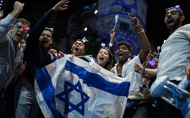 Illustrative. Israelis display their nation's flag as they revel in Independence Day celebrations, May 8, 2019. (Hadas Parush/Flash90)