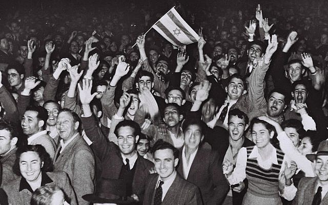 Jubilant residents celebrate in Tel Aviv with what would become the Israeli flag after the United Nations decision to approve the partition of Palestine, November 29, 1947. (Hans Pins/Israeli Government Press Office via Getty Images)
