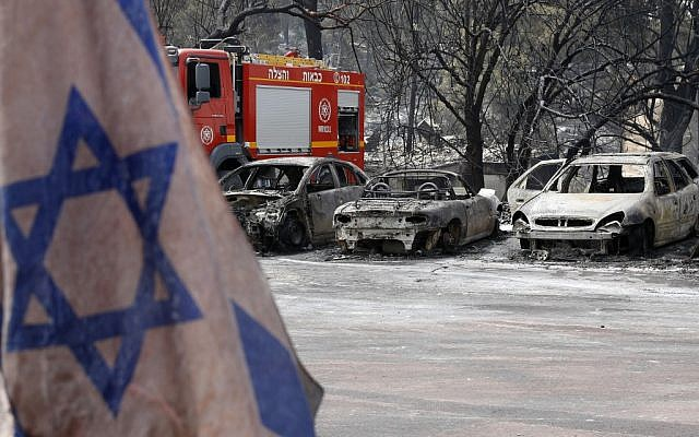 An Israeli flag is pictured in front of vehicles that were badly damaged by a fire amidst extreme heat wave in the village of Mevo Modi'im, in central Israel on May 24, 2019. (JACK GUEZ / AFP)