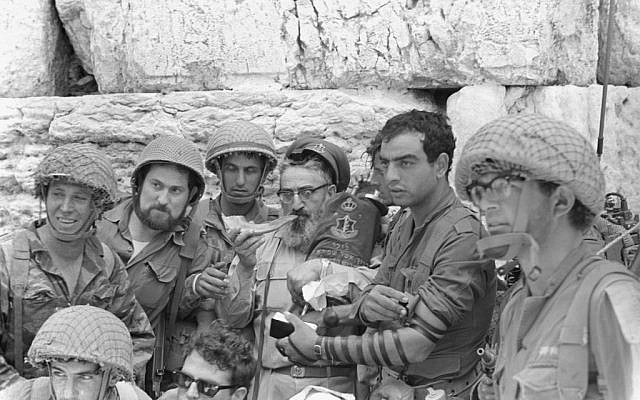 A group of soldiers surrounds then-IDF chief rabbi Shlomo Goren as he blows a shofar at the Western Wall in Jerusalem's Old City on June 7, 1967. (Bamahane Magazine/Defense Ministry's IDF Archive)