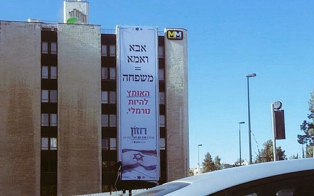 Giant poster hung on a Jerusalem hotel February 13, 2009 by the Hazon movement for a 'Jewish Agenda.' Following complaints, the hotel removed the poster several hours later. The slogan says 'Mother and Father - Family. The courage to live normally.' (Twitter)