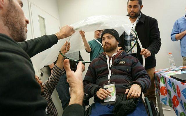 Tikkun Olam Makers teams create a hatchback canopy umbrella for the wheelchair of Drew McPherson (Courtesy)