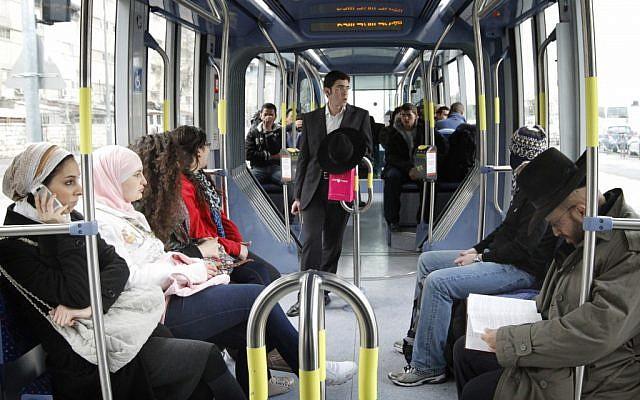 Illustrative: Ultra-Orthodox Jews and Arabs ride the Jerusalem light train on March 15, 2012. (Miriam Alster/Flash90)
