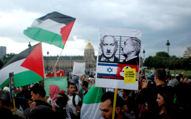 Protesters wave Palestinian flags and hold placards during a pro-Palestinian demonstration in Paris, France, on August 2, 2014. Israel bombarded Gaza on Saturdayafter accusing Hamas of destroying a humanitarian ceasefire by capturing a soldier whom the Islamists say was probably killed in Israeli shelling. (Photo by Alain Apaydin/ABACAPRESS.COM via Jewish News)