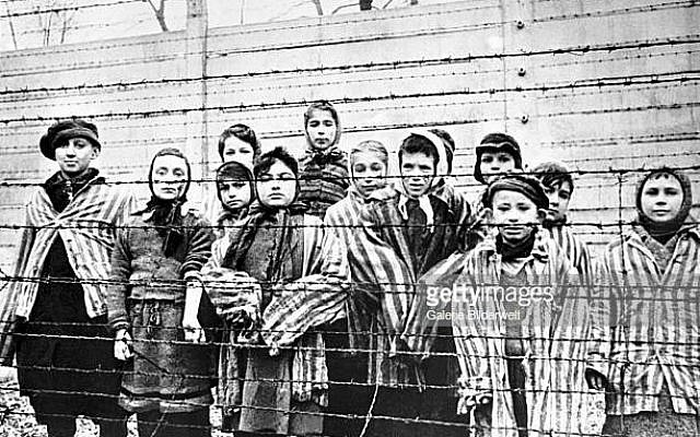 A group of child survivors behind a barbed wire fence at the Nazi concentration camp at Auschwitz-Birkenau in southern Poland, on the day of the camp's liberation by the Red Army, 27th January 1945. Photo taken by Red Army photographer Captain Alexander Vorontsov during the making of a film about the liberation of the camp. The children were dressed in adult uniforms by the Russians. The children are (left to right): Tomy Schwarz (later Shacham), Miriam Ziegler, Paula Lebovics (front), Ruth Webber, Berta Weinhaber (later Bracha Katz), Erika Winter (later Dohan), Marta Weiss (later Wise), Eva Weiss (later Slonim), Gabor Hirsch (just visible behind Eva Weiss), Gabriel Neumann, Robert Schlesinger (later Shmuel Schelach), Eva Mozes Kor, and Miriam Mozes Zeiger. (Photo by Alexander Vorontsov/Galerie Bilderwelt/Getty Images)