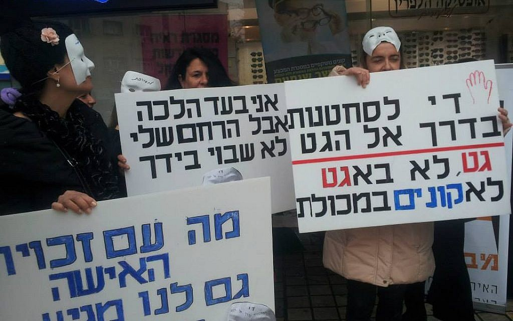 """Demonstrators holding signs on Aguna Day in protest of women trapped in marriages. The sign on the right reads """"Enough extortion on the road to a get,"""" referring to a Jewish divorce document. Picture courtesy of Mavoi Satum."""
