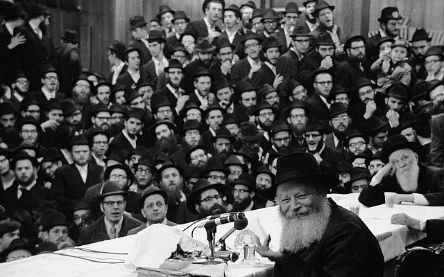 Rabbi Menachem Mendel Schneerson, at the microphone, shown in New York circa 1975. (Tim Boxer/Getty Images)