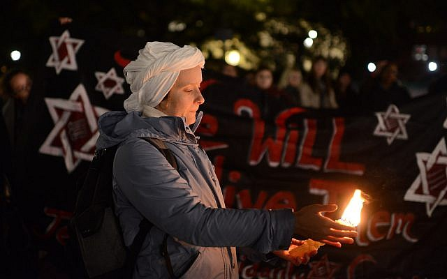 "A Jewish woman holding a candle, with a ""We Will Outlive Them"" banner in the background, at a New York vigil for the victims of the Tree of Life synagogue shooting in Pittsburgh. (Gili Getz)"