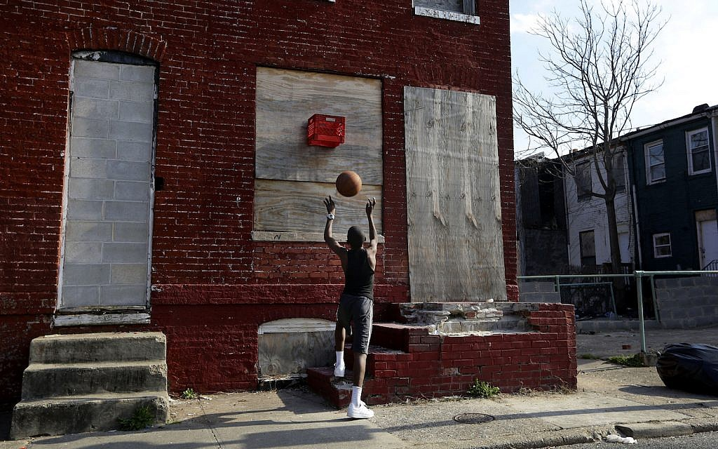 A boy shoots a basketball into a makeshift basket made from a milk crate and attached to a vacant row house in Baltimore. In 2013, an estimated 16,000 buildings were vacant or abandoned in Baltimore. April 8, 2013 (AP Photo/Patrick Semansky)