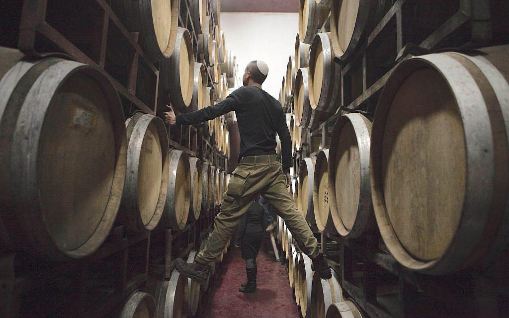 Israeli workers inspects barrels in a winery in the West Bank settlement of Psagot. Feb. 11, 2014 (AP Photo/Dan Balilty)