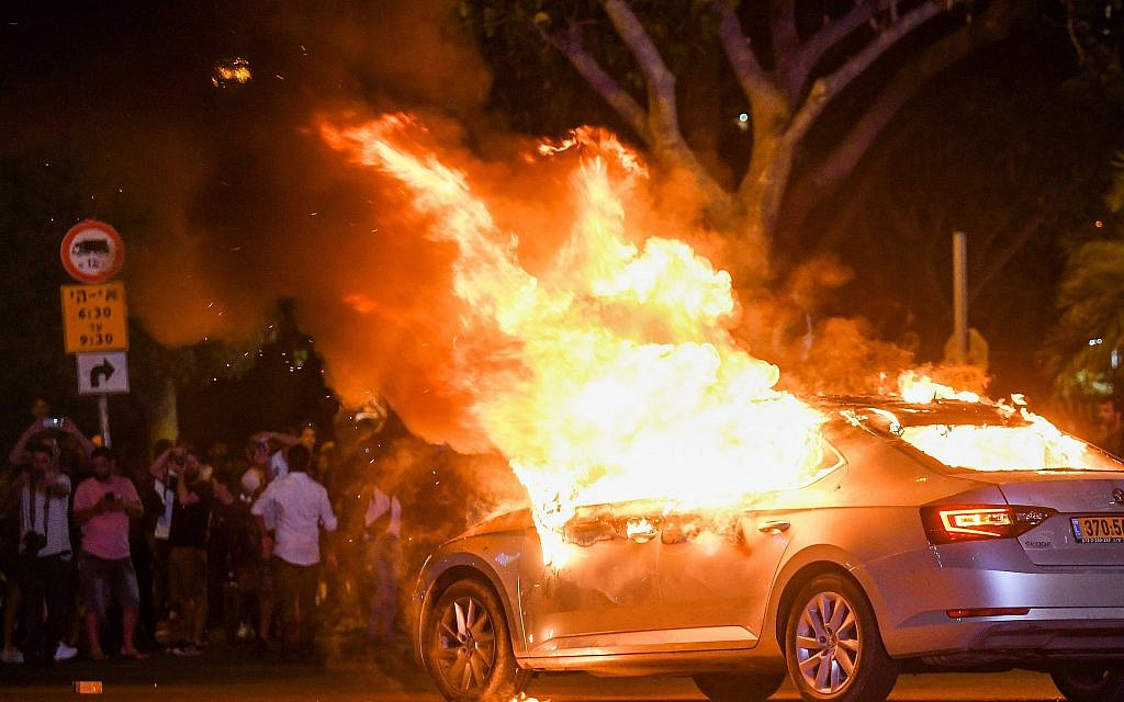 A car is seen on fire during a protest following the death of 19-year-old Solomon Tekah who was shot and killed in Kiryat Haim by an off-duty police officer, in Tel Aviv, July 2, 2019. (Flash90)