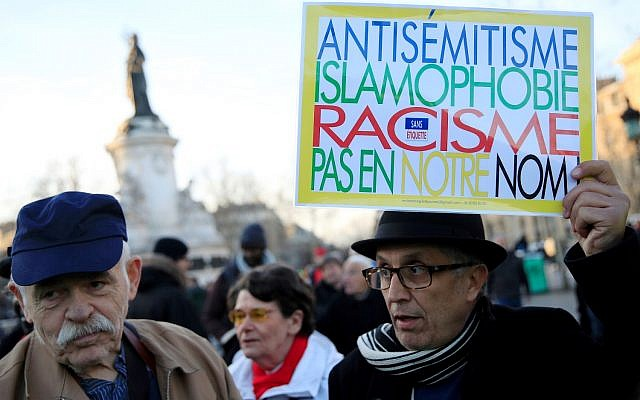 """FILE PHOTO: People attend a national gathering to protest anti-Semitism and the rise of anti-Semitic attacks in the Place de la Republique in Paris, France, February 19, 2019. The writing on the sign reads: """"Antisemitism, islamophobia, racism - not in our name"""".  REUTERS/Gonzalo Fuentes/File Photo"""