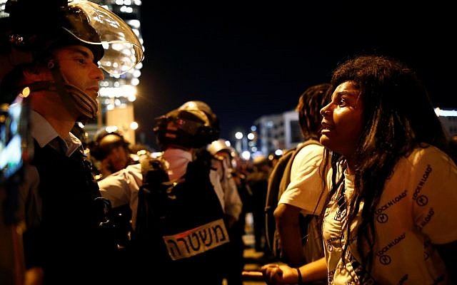 A protester reacts opposite a policeman during a protest for the death of 18-year old Solomon Tekah of Ethiopian descent, after he was shot by police, in Tel Aviv, Israel July 2, 2019. REUTERS/ Corinna Kern
