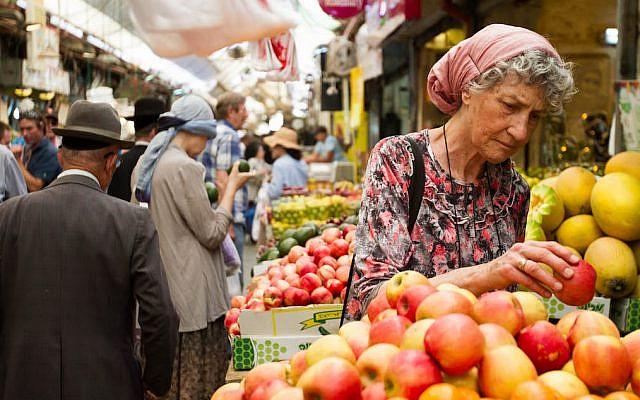 Illustrative. A woman picks out apples at the Mahane Yehuda market in Jerusalem on June 16, 2015. (Micah Bond/FLASH90)