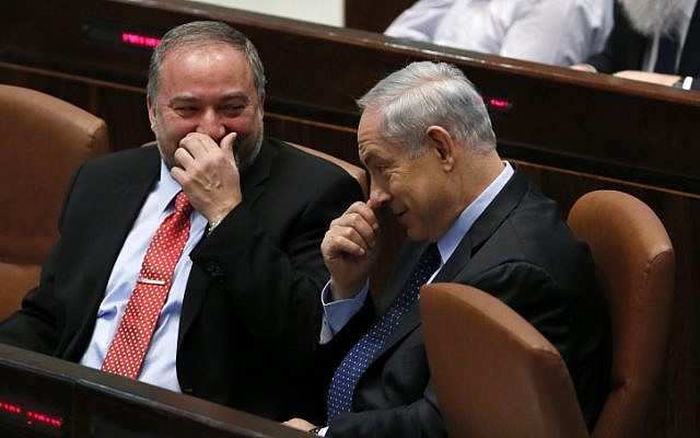 Then-foreign minister Avigdor Liberman seen with Prime Minister Benjamin Netanyahu in the Knesset's plenum hall, as the Knesset votes on the Governance Bill, which, among others, would raise the electoral threshold. March 11, 2014. (Miriam Alster/FLASH90/File)
