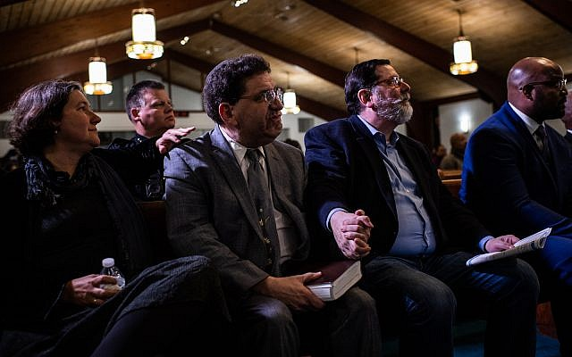 Pittsburgh Mayor Bill Peduto, right, holds hands with Rabbi Jonathan Perlman, who survived the shooting, at Rodman Street Missionary Baptist Church during service for the victims who were killed at the mass shooting at the Tree of Life Synagogue, on October 31, 2018, in Pittsburgh, PA. (Photo by Salwan Georges/The Washington Post via Getty Images)