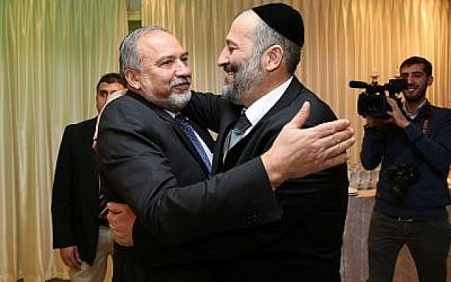 """Aryeh Deri (left), leader of the ultra-Orthodox Shas party, seen with head of the Yisrael Beytenu political party Avigdor Liberman at the """"Sheva Brachot"""" of Deri's daughter. December 23, 2015. (Yaacov Cohen/FLASH90)"""