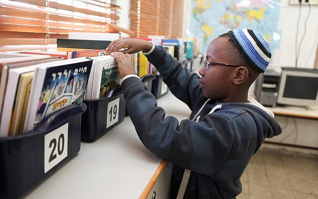 Student choosing a book for independent reading from the classroom library. Fall, 2017 (Courtesy of ICEI).