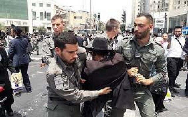 'Brothers in arms.' Police arrest an ultra-Orthodox Jew protesting the arrest of a draft dodger on August 2, 2018, in Jerusalem. (Israel Police)