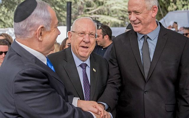 President Reuven Rivlin watches, as opposition leader Benny Gantz shakes hands with Prime Minister Benjamin Netanyahu hours before laying claim to his job (AFP Photo/YONATAN SINDEL)