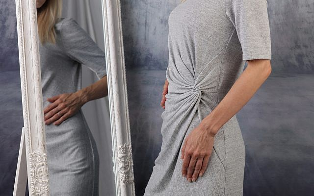 Illustrative. A woman looking at her body in the mirror. (iStock)