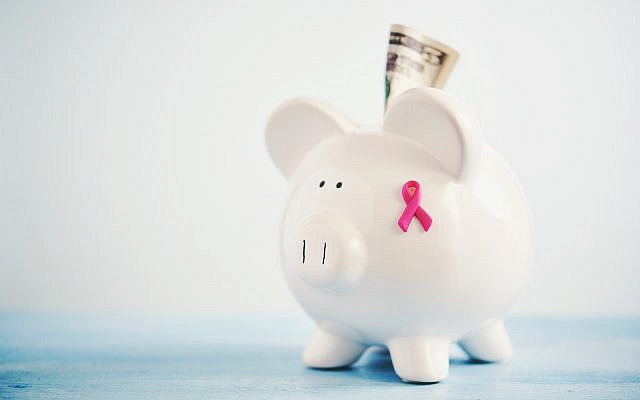Piggy bank with breast cancer awareness ribbon and cash to portray the concept of fundraising for breast cancer awareness and research. (Catherine Lane/Getty Images)