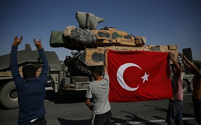 Local residents applaud as a convoy of Turkish forces trucks transporting tanks is driven in Sanliurfa province, southeastern Turkey, at the border with Syria, Saturday, Oct. 12, 2019.  (AP Photo/Lefteris Pitarakis via Jewish News)
