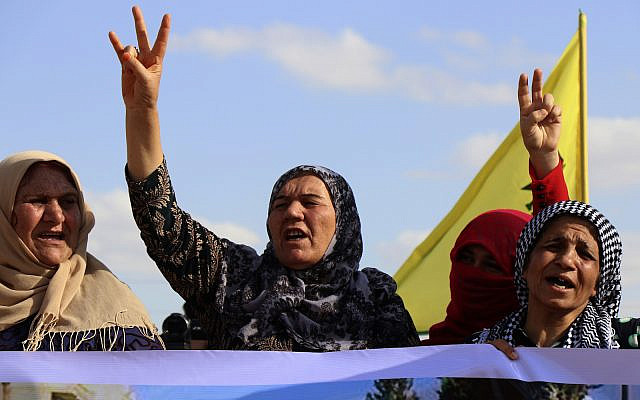 Kurdish women flash victory signs and shout slogans, as they protest against possible Turkish military operation on their areas, at the Syrian-Turkish border, in Ras al-Ayn, Syria, Monday, Oct. 7, 2019. (AP Photo)