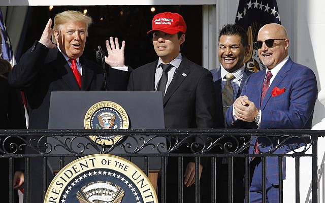 President Donald Trump, left, reacts as Washington Nationals catcher Kurt Suzuki walks to a podium during an event to honor the 2019 World Series champion Nationals at the White House, Monday, Nov. 4, 2019, in Washington. Standing alongside Suzuki are manager Dave Martinez, second from right, and general manager Mike Rizzo. (AP Photo/Patrick Semansky)
