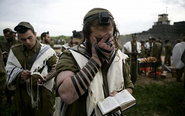 Illustrative: Religious soldiers of the Netzah Yehuda Battalion pray while completing the final stages of a 40 kilometer journey in 2010. (Abir Sultan/Flash90)
