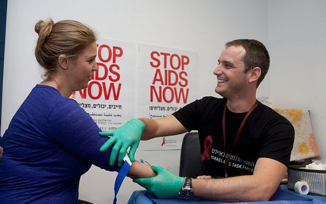 Illustrative: Former Israeli MK Adi Kol does an HIV test in the Israeli parliament, as part of a blood drive to identify those who had contracted HIV/AIDS, performed by the Israel Aids Task Force on November 25, 2013. (Flash90/File)