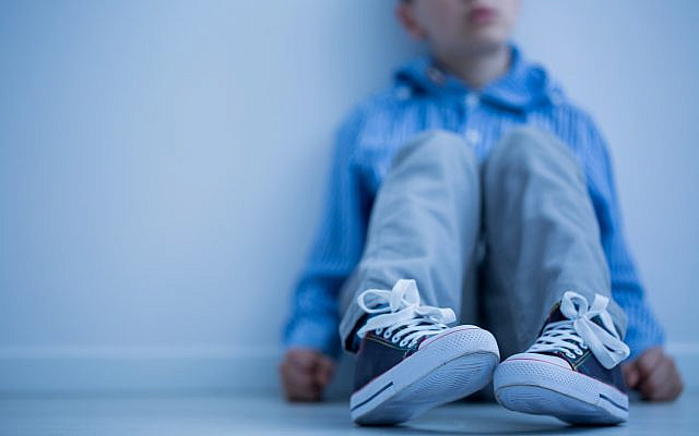 Illustrative. A boy sits alone, on the floor. (iStock)