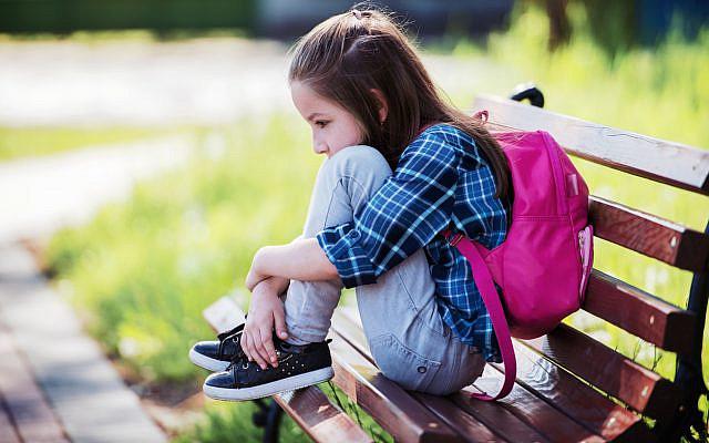 Illustrative. Unhappy schoolgirl, sitting in the park. (iStock)