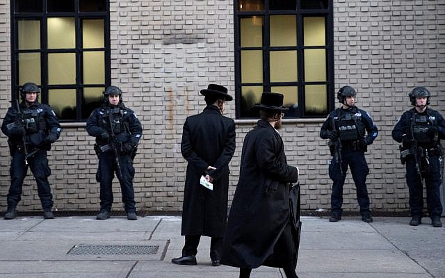 New York City police guard a Brooklyn synagogue, prior to a funeral for Moshe Deutsch, December 11, 2019, a rabbinical student from Brooklyn, who was killed in the shooting inside a Jersey City, NJ kosher market. (AP Photo/Mark Lennihan)