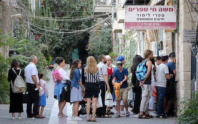 Israelis stand in line at the entrance to a bookstore ahead of the upcoming school year. August 24, 2017. (Gershon Elinson/Flash90)