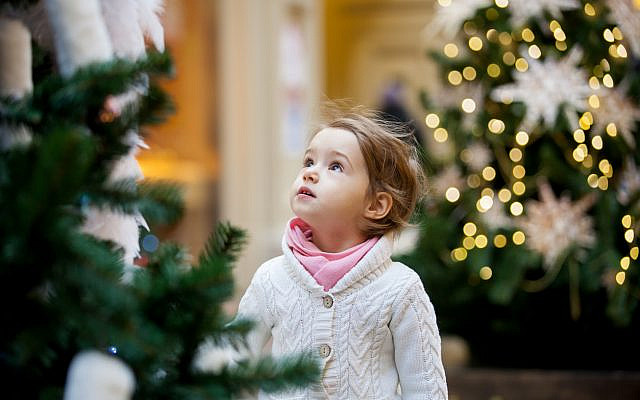 Illustrative. A girl looks with wonder at the beautifully decorated Christmas trees in the shopping mall. (iStock)