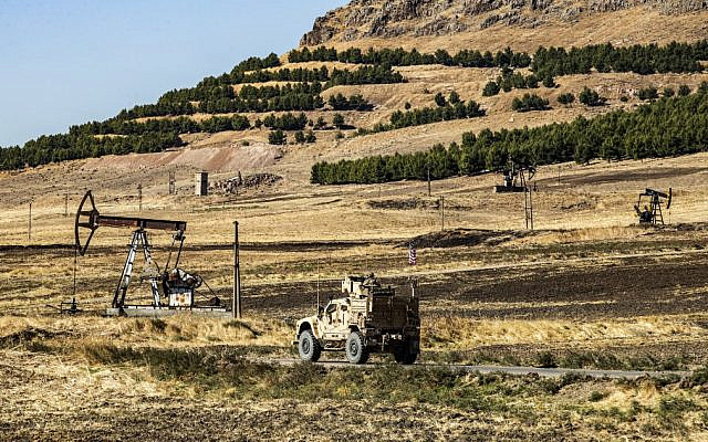 A US military armored vehicle drives in a patrol past a pumpjack operating at an oil well in Rumaylan in Syria's northeastern Hasakeh province on November 6, 2019. (Delil SOULEIMAN / AFP)
