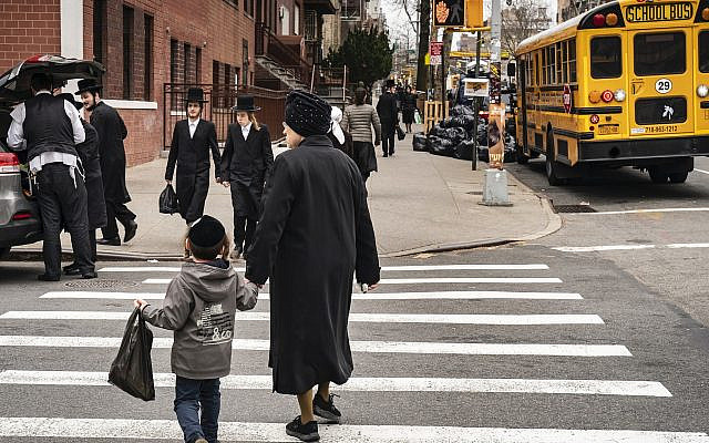 Illustrative. Pedestrians walk past a yeshiva in the South Williamsburg neighborhood of Brooklyn, New York, April 9, 2019. (Drew Angerer/Getty Images via JTA)