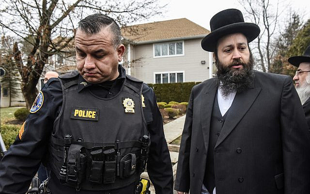 A member of the Ramapo police stands guard in front of the house of Rabbi Chaim Rottenberg, Dec. 29, 2019, in Monsey, New York. Five people were injured in a knife attack during a Hanukkah party. (Stephanie Keith/Getty Images)