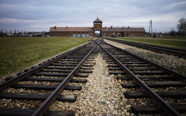 In this Dec. 7, 2019, photo, railway tracks from where where hundreds of thousands of people were directed to the gas chambers directed to the gas chambers to be murdered, inside the former Nazi death camp of Auschwitz Birkenau or Auschwitz II, in Oswiecim, Poland. World leaders will gather twice to mark the 75th anniversary of the liberation of the Auschwitz-Birkenau concentration camp _ once on Thursday, Jan. 23, 2020, in Jerusalem and again on Jan. 27 at the Auschwitz site in southern Poland. The fact that there will be two competing ceremonies reflects how politically charged World War II remains for nationalist governments in Russia and Poland. (AP Photo/Markus Schreiber, File)