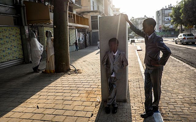 Two Eritrean boys stand outside a church in south Tel Aviv (source: PRI)