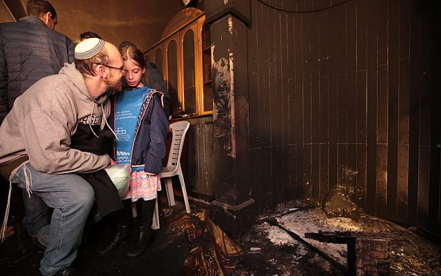 "A father and daughter examine the damage to the mosque burned in a ""Price Tag"" attack. Photo credit: Yossi Zamir, Tag Meir."