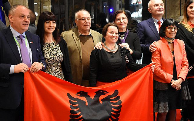 Bardhyl Canaj, Albania's ambassador to Israel, at far left, holds up one corner of the Albanian flag. Joining him are members of Israel's tiny Albanian Jewish community and Albanian President Ilir Meta, at far right. (Larry Luxner)