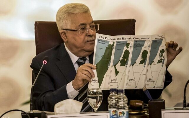 Palestinian president Mahmud Abbas holds a placard showing maps of (L to R) historical Palestine, the 1947 United Nations partition plan on Palestine, the 1948-1967 borders between the Palestinian territories and Israel, and a current map of the Palestinian territories without Israeli-annexed areas and settlements, as he attends an Arab League emergency meeting discussing the US-brokered proposal for a settlement of the Middle East conflict at the league headquarters in the Egyptian capital Cairo on February 1, 2020. (Photo by Khaled DESOUKI / AFP)
